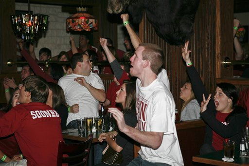 Sooners' fans react to their team scoring  during  the  championship  game. The patrons  were at a bar in Norman , Oklahoma  ..............