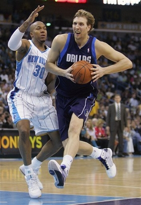 Dirk  Nowitzki  of  the  Dallas  Mavericks drives to the  basket  whilst   trying  to  evade the defensive play  of the Hornets'  David West .