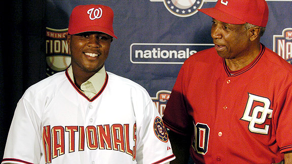 Esmailyn Gonzalez  as  he's  known  the  Washington Nationals  but  the  player's  actual  given  birth  name  is  Carlos Alvarez  Daniel  Lugo.  He's  seen  here  signed  as a  top prospect   with  then  coach  Frank  Robinson.