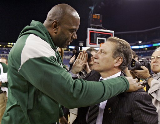 Former  Michigan State  player and  NBA  great  Earvin 'Magic' Johnson  who  was  courtside  congratulates   coach  Tom Izzo on the team's  victory.