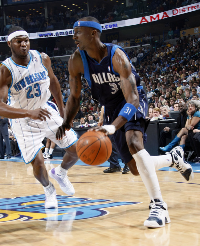 Jason  Terry of  the Mavericks  attempts to  drive  past  the Hornets' Devin Brown .........
