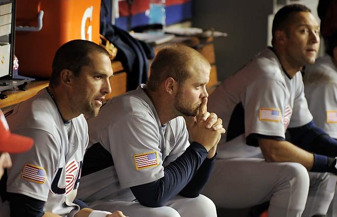 Derek  Jeter  far  right  seated   in  the  dugout  knowing  that the  inevitable  is  about to  happen.  The  US  team  would   go  on  to  lose  in the  semi  finals  of  the  World  Baseball  Classic  to  Japan  (9-4) .