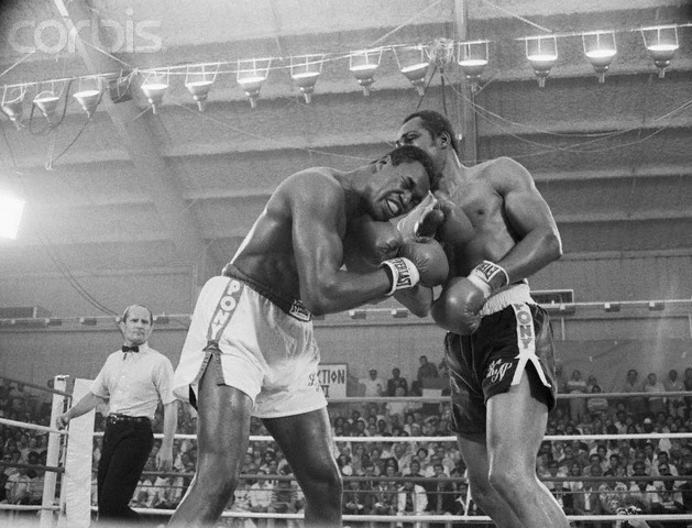 Ken  Norton  faces  Larry Holmes  with  referee  Mills  Lane  of  Las Vegas  overseeing  the  bout.  The  fight itself  was held  Caesar's  Palace  Hotel & Casino  , Las Vegas,. Nevada.