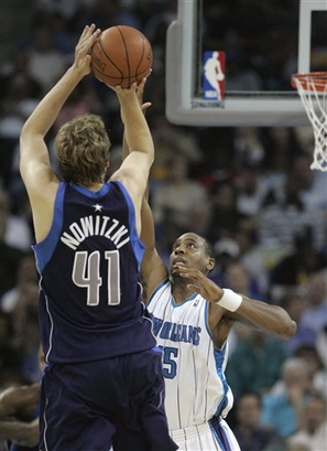 Nowitzki  shoots the long  range  jumper over the  head  of the  Hornets' Rasual  Butler   during  the  game.