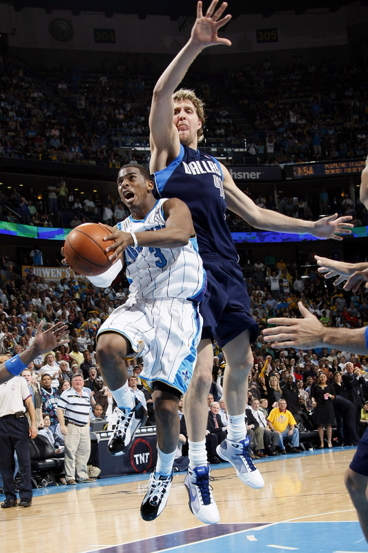 Paul goes for the  layup  whilst  Nowitzki tries  to  negate the offensive  play during  the  game.