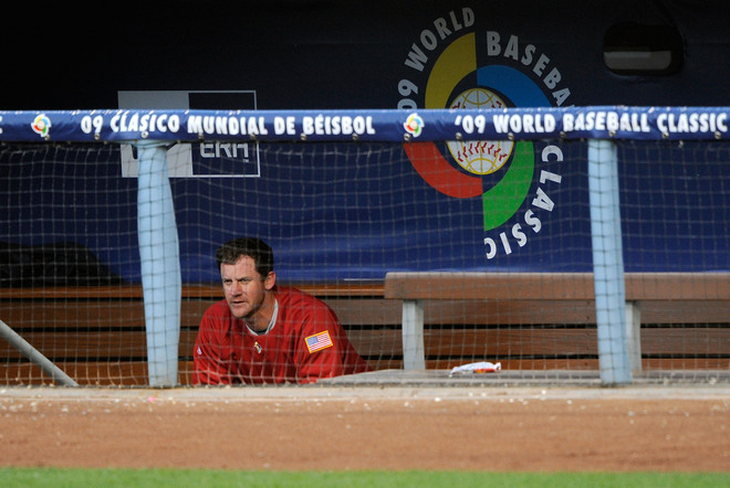 Roy  Oswalt  the  starting   pitcher  for  team  USA  sits  in the  dugout  watching  the  game's  progression.  Oswalt   had  one  of those   games  that  even  he  would  no  doubt  rather  forget  .