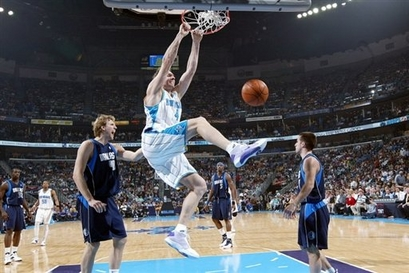 Sean  Marks   of  the New  Orleans  Hornets   gets  up  for the dunk   during  the game  against  the  Dallas  Mavericks.  The  defensive  play   of  the   visiting  team  was  negligible  throughout much of  the  game.