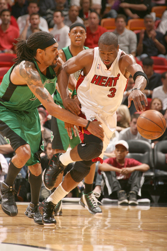 The Miami  Heat's  Dwyane  Wade contests  a loose   ball  with the  Boston Celtics' Mikki  Moore  during  the  game.