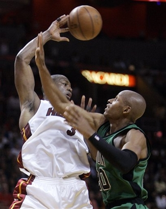 Wade passes the ball  over  the  outstretched  arm  of the  Celtics'  Ray  Allen .