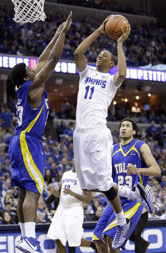 Wesley Witherspoon  of Memphis  drives  to  the  basket  as Tulsa's  Ray Reese and  Jerome  Jordan(23) looks on.