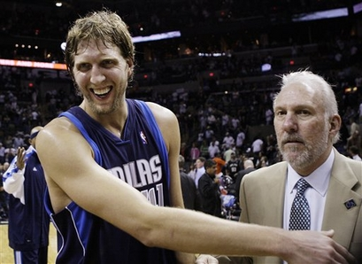 A joyful   Dirk  Nowitzki  is  congratulated  by   a  somewhat  solemn    Gregg  Popovich .