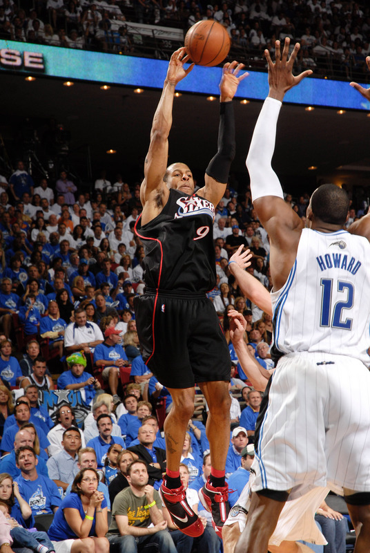 Andre' Iguodala  of  the  76ers attemmpts the  jump  shot over the  outstretched  arms  of the  Magic's  Dwight  Howard.   Iguodala would  go  on to  score  20 pts  for  the  76ers  in their triumph  over the Orlando Magic.  They  now hold  1-0  in the best  of  seven  game series.