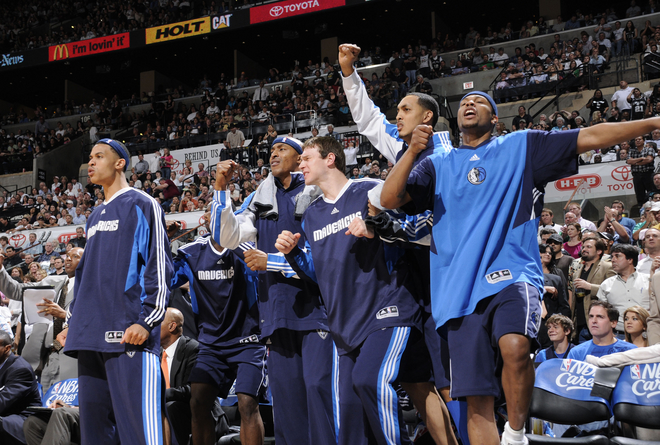 In the  waning  moments of the  game  the  Mavericks'  bench  players are   jubilant .