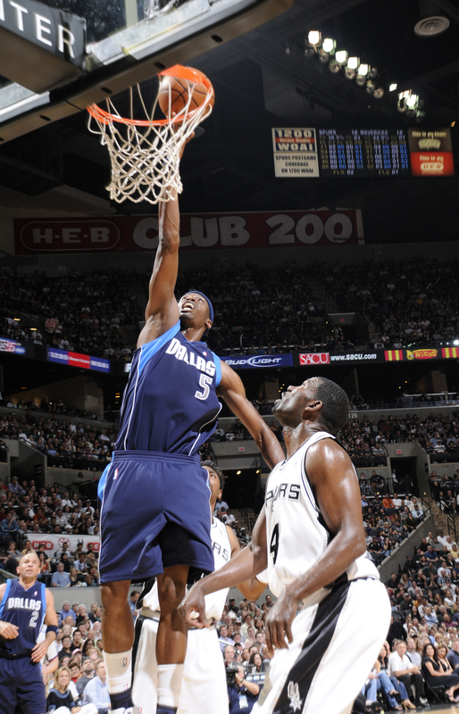 Josh Howard  of  the  Mavericks  dunks the  ball while the  Spurs'  Michael  Finley   looks  on  in   game 5 of  the  playoff  series between  the two teams.