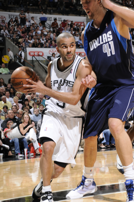Tony  Parker  of  the  Spurs  tries to  evade the  much  larger  presence  of  the  Mavericks'  Dirk  Nowitzki.