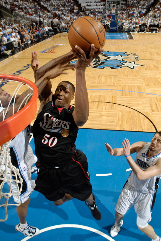 Theo  Ratliff  of the 76ers makes  the   dunk  over the   defensive  presence  of the  Magic's  Hedo  Turkoglu  and  Tony Battie .