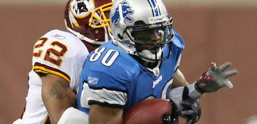Lions'  wide   receiver   Bryant   Johnson  is   tackled   by  the  Redskins'  defensive   player   Carlos   Rogers  .     The   Lions  would  go  on  to  defeat  the  Redskins  19-14   in   a  game  played  at   Ford   Field    in  Detroit   ,  Michigan.    picture  appears  courtesy  of   ap/photo/  Carlos   Osorio   ....................