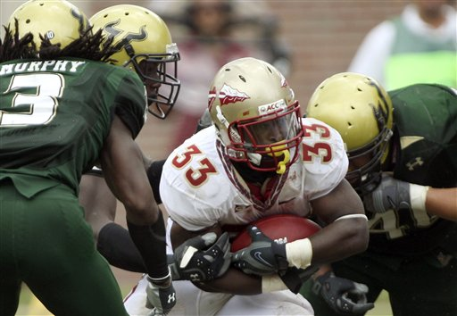 Noles' running  back Ty Jones  is surrounded  by  Bull  defensive   players  as  he   attempts  attain  some  yardage  in  the third  quater.      picture  appears   courtesy  of ap/photo/  Phil Coale  .................