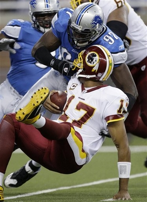 Redskins' quarterback  Jason Campbell (97)  is  face masked   by  Lions'   defensive  player  Jason  Hunter (97)   during  the  game  played  between  the   two   teams  at   Ford  Field   ,  Detroit  ,  Michigan.      The   Lions   would   go  on  to   defeat  the  Redskins   19-14.          picture  appears   courtesy  of   ap/photo/   Paul  Sancya  .........................