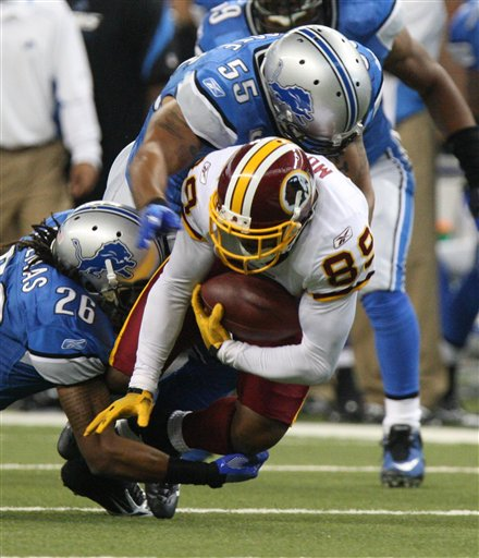Redskins'  wide  receiver   Santana  Moss (89) is  tackled  by  Lions'  defensive   players    safety ,  Louis  Delmas (26)  and   linebacker,  Larry   Foote (55)   during  the  game.    The  Lions  would   go  on to  defeat  the  Redskins   19-14  and   halt  their   19   game    regular  season  losing  streak.        picture  appears  courtesy  of  ap/photo/  Carlos   Osorio   .................................