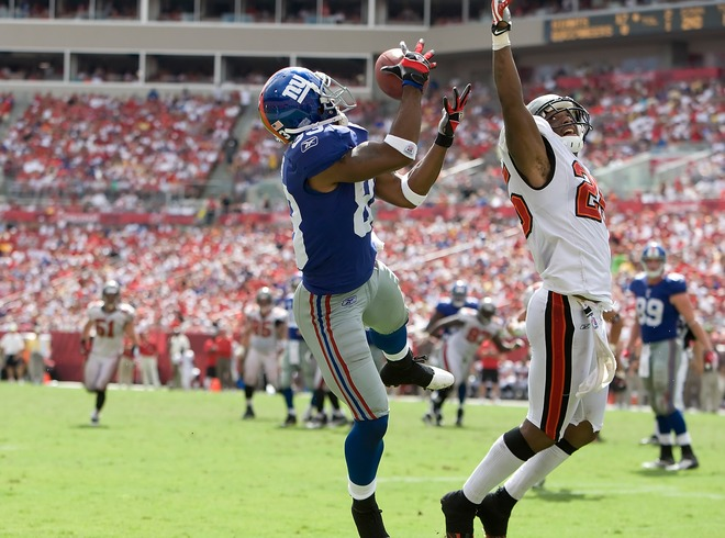 Giants'  wide  receiver  Sinorice Moss (83)  catches  a  touchdown  pass   over the  shoulder  of   Bucs'  cornerback  Aqib  Talib (25)  ensuant to  the  Giants   24-0  defeat  of  the  Buccaneers  at  Raymond   James  Stadium  in  Tampa  ,  Florida  .    picture appears courtesy of   getty  images/  J  Meric  ........................