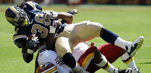 Steven  Jackson  of  the  Rams   is   upended  during  the   game  played  against  the  Redskins   by DeAngelo  Hall.    The  game  itself   was  something  of   an  eyesore  as  a  spectacle  for  those   in  attendance at   Fedex  Field  in  Landover, Maryland.   The  game  was  won   by   the  Redskins   9-7  over  the    St  Louis  Rams.     picture  appears  courtesy of   ap/photo/  Rob  Carr  ......................