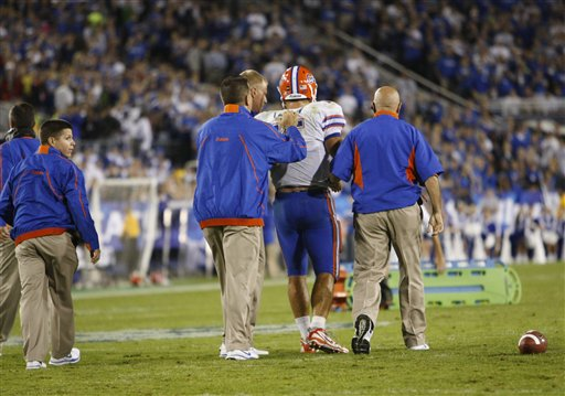 Tebow is   helped  off  the field   as  a  stretcher  lies  in the  background.   The  player  was  determined  to  have   suffered   a  second   degree  concussion     during   the  game.     picture  appears  courtesy  of ap/photo/  Ed  Reinke  .........................