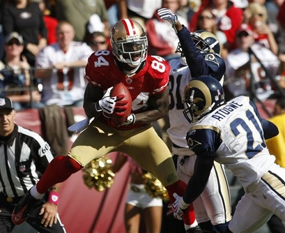 Forty Niners' wide  receiver  Josh  Morgan (84)  catches a  24 yard  toucdown  pass  during  the  game  as   he's  surrounded   by  Rams'   players   cornerback    Justin King (31)  and   safety   Oshiomo  Atogwe (21)   during  the   fourth   quarter  of  the  game .          picture  appears  courtesy  of ap/photo / Paul  Sakuma    .......................