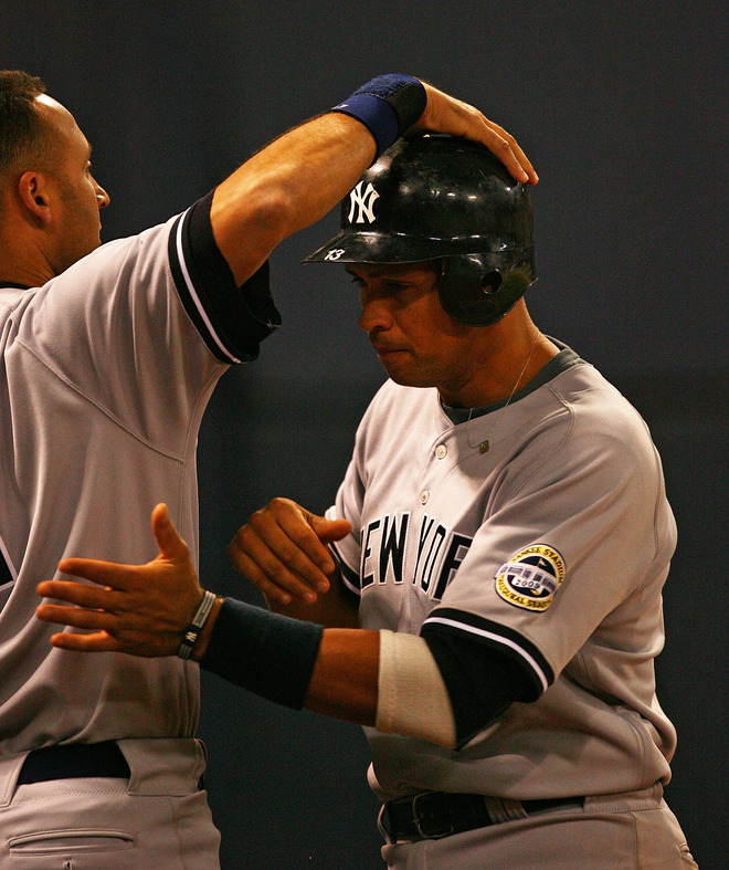 Yankees  third  baseman   Alex  Rodriguez  gets  a  pat  on the  head   from  team   captain   Derek  Jeter after    he  scored a  run  against  the  Minnesota  Twins  in  game 3  of  the  ALDS  game   played  at the  Hubert  Humphrey  Metrodome  in  Minneapolis,  Minnesota,.     picture appears  courtesy of  getty images/ Johnathan Daniel ................