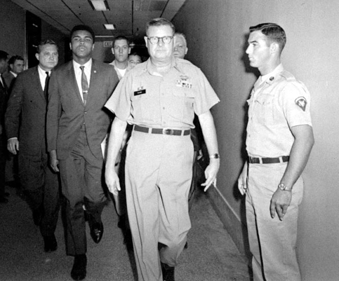 Ali  seen   here   being   escorted   away   by  MP's  after  having  been  found   guilty   for  refusing  to  be   inducted   into  the   US  Army.     The   verdict  was   later   overturned   by  the  US  Supreme  Court   in  1971.    As  a   result   he   would   miss   3  1/2  years    from  the  sport  of    boxing.      picture  appears   courtesy  of   si/sports illustrated / id.cnn/turner/archives