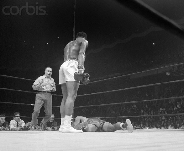 Ali    stands over the  prostrate   body  of    boxer  Zora  Folley   , whom  he  defeated  in the   defense  of  his  world  heavyweight   titLe   held   at  Madison  Square    Garden  New  York   in  March  of  1967.    Ali   won  the   fight   with  a   7th  round   knockout  of  the   challenger     and  it  would  be   his   last   professional  bout  before  being   stripped  of  the  heavyweight  title    that   same   year.  His  return  to  the  ring   would  be  almost  four  years  later when  he  fought  Jerry   Quarry  in  Atlanta, Georgia , in  October  of   1970.      picture   appears    courtesy   of    corbis   / Bettman    ...............   copyrighted  material  @   all   rights   reserved .........................