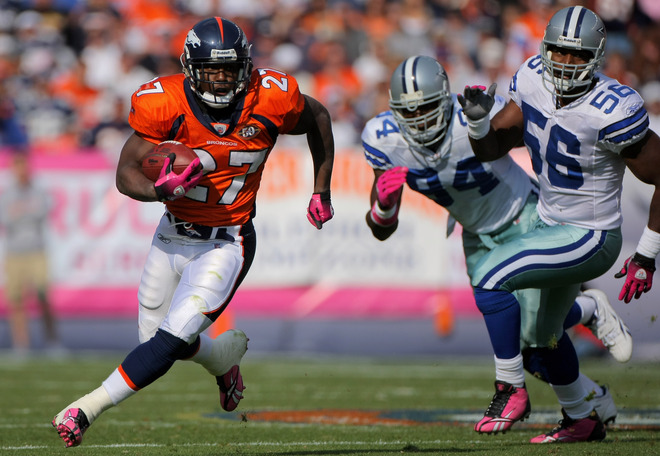 Broncos' running back   Knowshon  Moreno    evades  Cowboys'  defensive  players   DeMarcus Ware (94)  and  Bradie  James  (56)  .      picture appears   courtesy  of   getty  images  /  Doug Pensinger  ............................