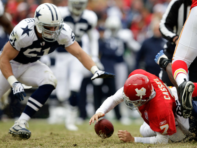 Chiefs'   quarterback  Matt  Cassel (7)  having   fumbled  the  ball  during  the  scrimmage   looks to retrieve  the  ball    in a  game  played  against the  Dallas Cowboys  at  Arrowhead  Stadium  in  Kansais  City  ,   Missouri.   Looking  on  is  the  Cowboys'   player  ,  Keith  Brooking .    picture appears   courtesy  of  getty  images/  Jamie  Squire  .....................