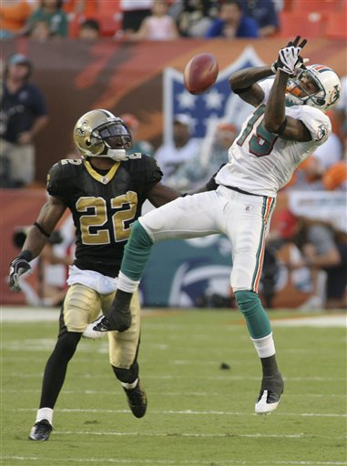 Dolphins'  wide   receiver   Ted Ginn Jr.(right)  can't  hang  on  to  the  ball   causing an   interception  that   would  be   returned   for  a  touchdown    by the  Saints'  cornerback    Tracy  Porter  (22) .      picture appears  courtesy  of  ap/photo/ Jeffrey  M.  Boan   ................