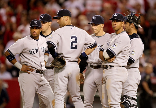 Joe Girardi  (center)  in  the  midst  of   his  players    on the   mound  to   discuss   a  strategy  to  be  used   during the  game    against the    Los  Angeles  Angels.    Also  in   picture   is  Yankees'  captain  Derek Jeter (2)  and    And  Alex  Rodriguez   amongst the  other  players.        picture   appears    courtesy   of  getty  images/   Stephen  Dunn   ............................