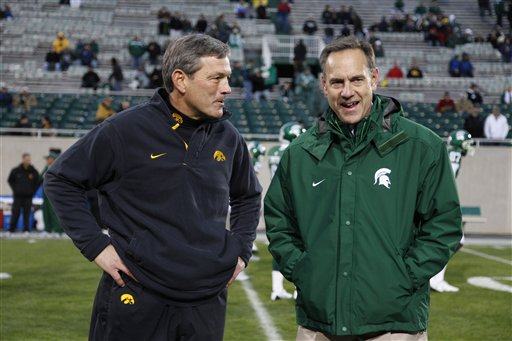 Iowa (Hawkeyes)  coach  Kirk  Ferentz,  left, stands  alongside   Michigan  State  coach  Mark  D'Antonio  prior  to  the   game  between their  two   teams   played   in   East Lansing,  Michigan.     The   Hawkeyes   would  go  on  to defeat  the  Spartans  15-13  to   remain   unbeaten  in  the   Big  Ten  as  they   sit  atop  of  the  standings  within  the  conference.   The  Hawkeyes   are  also    ranked  #4  in  the BCS Poll  standings.  And  they  are   one   of the   seven   ubeaten  teams  within  the   top   ten  of the  BCS   rankings  at  present.   picture  appears  courtesy  of   ap/photo/  Al  Goldis   .........................