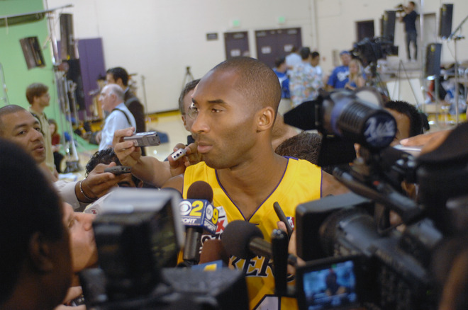 Kobe  Bryant  speaks to  members  of  the  media   at the  team's   media  day  at  the   opening  of  their  training   camp  at  the  Toyota  Center   ,  the  team's training   facililty  in  El  Segundo  ,  California.     The   Finals  MVP  of  last  year  is   relishing  the  challenge  of   opening   up  the   2009-10  season  as  the   defending   NBA  champions  and   is  looking  to   successfully   defend  that  title.       picture  appears  courtesy  of   nbae/getty  images/  Evan  Gole   ................