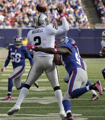 Giants'  linebacker  Mathias Kiwanuka   ,right,  strips    Raiders'  quarterback  JaMarcus   Russell  of  the ball    in  the   third  quarter  of the  game  played between  the   two  teams  played  at  Giants   Stadium ,  East  Rutherford,  New  Jersey  .  The   Giants   would   defeat  the  Raiders   in  a   44-7   rout   .         picture  appears  courtesy  of    ap/photo/ Bill   Kostroun  ...................