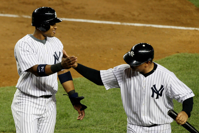 Nick   Swisher   (33)  of   the  New  York Yankees  and    teammate    Robinson   Cano   celebrate  a   run  being   scored    of  a   single  by  Johnny   Damon.     The  Yankees  are   on    the   cusp of    winning the    AL  pennant   as  they've    now   taken   a  3-1  lead   in  the  bottom  of the    eighth    in    game  6  of  the  ALCS.    They  lead  the   Los  Angeles   Angels    3-2   in  the  best  of  the   seven  game   series.     The  winner   will   meet   the   Philadelphia  Phillies  for  the  World  Series  .     picture  appears courtesy  of     getty  images /  Jim   McIsaac   ......................