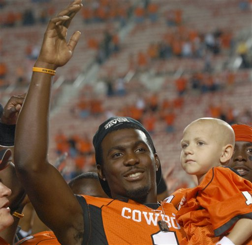 Oklahoma   State   wide  receiver   Dez  Bryant   seen  here   holding   cancer  patient   Cason  Tacket, right,     just   after the  Cowboys'   56-6   triumph over   Grambling    State   in a   game   played   at  Cowboys' Stadium  in  Stillwaterter  ,  Oklahoma,.       The   player  is   now  at  the  center  of  an   ongoing   investigation  by  the  NCAA  as  to   his   interaction   with  former  NFL  player   Deion  Sanders.    The  NFL great   has  stated  that   nothing   untoward  took   place   between    he   and   Bryant.      picture   appears    courtesy  of  ap/photo/file-/ Brody  Schmidt    .............................