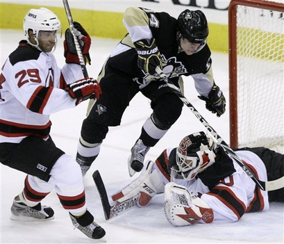 Chris  Kunitz (center)   of  the  Philadelphia  Penguins  collides  with   New  Jersey  Devils'   goal tender   Martin Brodeur (lower right )    during  a   regular  season  game .  Looking  on  is   Devils'   defenseman   Johnny  Oduya   (left)  .    The   Devils   would    go  on  to   defeat  the  Penguins    4-1 in  the  game  played   in  Pittsbugh  ,  Pennsylvania ,.      picture  appears  courtesy  of   ap/photo/  Gene  J.   Puskar     ...........................