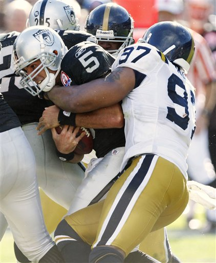 Raiders'  backup  quarterback  Bruce  Gradkowski  (5) is  about  to  be  brought  down   for the  sack by   Jets'   linebacker  Calvin  Pace    in  the   third   quarter  of the  game.   picture appears  courtesy  of  ap/photo/  Ben  Margot  .....................