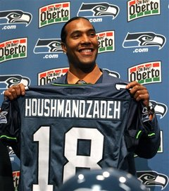 Seahawks'   wide  receiver   T J Houshmanzadeh   shows   off  his   new  jersey   replete  with  his   name  and   number.  Pity   however  the  player  has   yet  to  show  the  form  for  his  new  team  that  made   such  a  highly  sought  after   free  agent  .    picture  appears  courtesy  of    ap/photo/  Kevin  P. Casey  .............