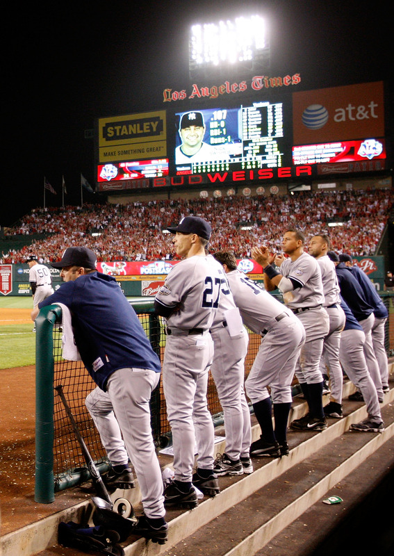 Yankees'    players   in  the  dugout   watch  as   teammate  Nick  Swisher  is  up  for  an  at  bat   in   the  ninth  inning  of   game   of the  ALCS  between the  New York  Yankees  and  Los  Angeles Angels .    The   Angels   would   go  on  to  defeat  the  Yankees  7-6   in   the  game  played  at  Anaheim  Stadium  ,  Anaheim , California.         picture  appears   courtesy  of   getty  images/ Harry  How  ......................