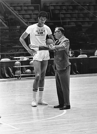 A young Lew Alcindor  listens  attentively  to his  coach  and mentor  John Wooden    on  the  Bruins  famed  basketball  court