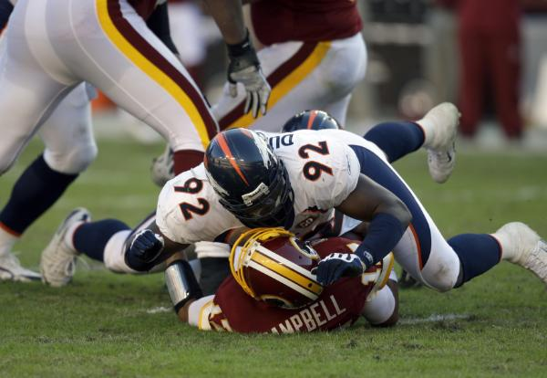 The Broncos'  Elvis  Dumervil  sacks  Washington  Redskins'  quarterback,  Jason Campbell,  in the second  quarter  of  Sunday's  NFL  game  played   at Fedex  Field ,  Landover ,  Maryland .   The  Broncos  would  suffer their  third  successive defeat   ,  losing   27-17   to  the  struggling  Redskins.     picture  appears   courtesy  of  ap/photo/ Rob  Carr  .................