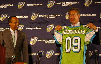 Calfornia  Redwoods'  owner  Paul  Pelosi   holds  up   a  Redwoods'  jersey  at the  unveiling   of  franchise's    formal   entrance   to the  UFL .    picture  appears   courtesy  of  sfblog.com   /  Joe  Eskenazi  ..................