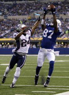 Colts' wide  receiver  Reggie Wayne  makes  a  catch   while  Pats'  defender  Johnathan  Wilhite  is  unable to  negate the play  in a  game  played  at the  RCA  Dome in Indianapolis , Indiana .   The  Colts   would  go on to  defeat the  Patriots  35-34 in  a  highly  competitive  and  entertaining  game.    picture  appears  courtesy  of  ap/photo/ Darron  Cummings ....................