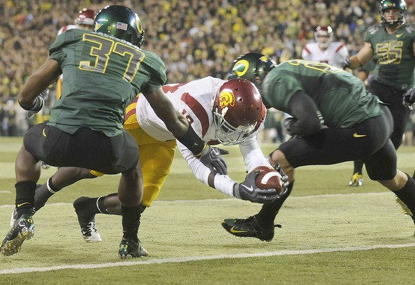 Damien  Williams  of  USC  dives   into the  endzone  for  the   score  in  between  Ducks'   players    Talmadge  Jackson  III  and   John  Boyett   during  the   second   quarter  of  the   PAC-10 conference   played  between  the  two divisional  rivals  .  picture  appears   courtesy of   latimes.com  / Wally  Skalij  .................