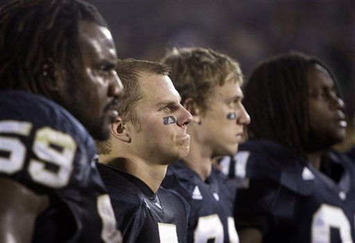 Jimmy  Claussen , second  from the  left  alongside his  teammates  on the  sidelines  watch  as  the Notre  Dame alma mater   song  is  sang  after  the  team's  inexplicable  23-21   loss to  Navy in  a  game  played  in South Bend ,  Indiana ,.   picture appears courtesy  of ap/photo/ Darron Cummings